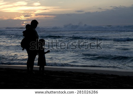 Silhouette of woman and children at the beach at sunset - stock photo