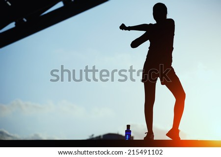 Silhouette of woman doing sports outdoors, beautiful female jogger doing workout during the evening training outdoors, attractive female runner stretching before her workout, woman fitness silhouette - stock photo