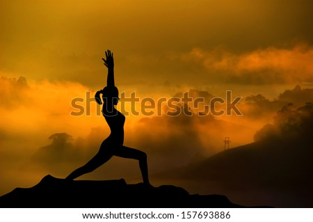 Silhouette of woman doing yoga meditation during sunrise with natural golden sunlight on mountain. - stock photo