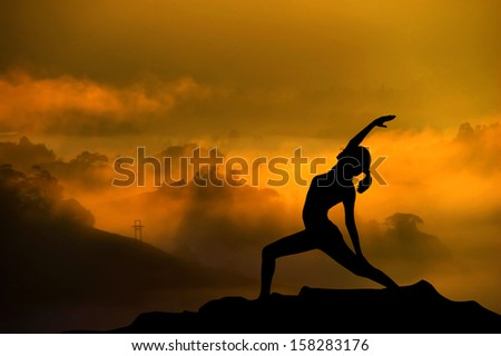 Silhouette of woman doing yoga meditation during sunrise with natural golden sunlight on mountain.