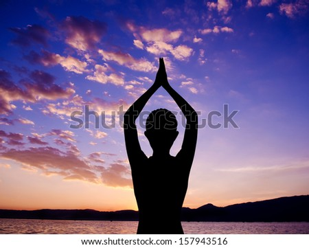 Silhouette of woman doing yoga meditation during sunset with natural golden sunlight at outdoor beach. - stock photo