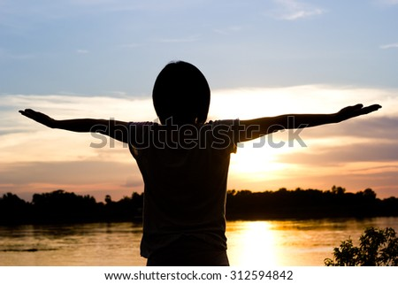 Silhouette of woman exercising over beautiful sunset background.