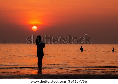 Silhouette of woman holding smart phone, standing on the beach at sunset