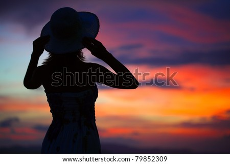 Silhouette of woman in hat on colorful and vivid sunset background - stock photo