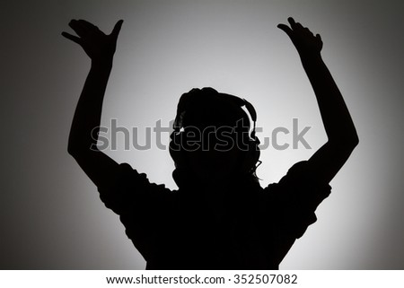 Silhouette of woman in headphones with raised hands listening to music - stock photo
