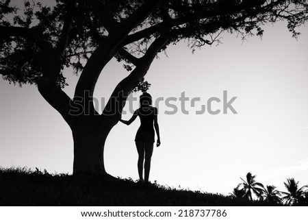 Silhouette of woman in the park - stock photo