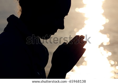 Silhouette of woman in  type, which sits ashore  and prays fold arms - stock photo