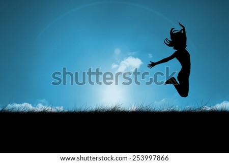 Silhouette of woman jumping against blue sky over grass - stock photo