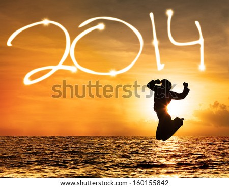 Silhouette of woman jumping and drawing 2014 at sunset - stock photo