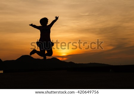 Silhouette of woman jumping in front of the sunset on the hill
