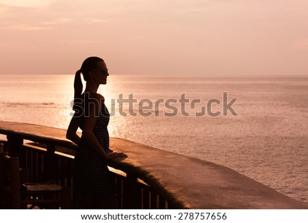 Silhouette of woman looking out a the beautiful sunset.  - stock photo