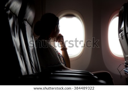 Silhouette of woman looks out the window of an flying airplane. Passenger on the plane resting beside the window.  - stock photo