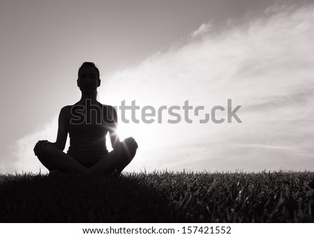 Silhouette of woman meditating - stock photo
