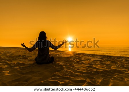 Silhouette of woman meditating on the beach, practicing yoga during sunset over the sea
