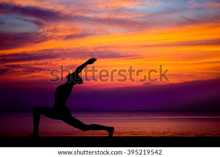 Silhouette of woman on the background of the stunning sea and sunset making yoga poses, spirit exercises