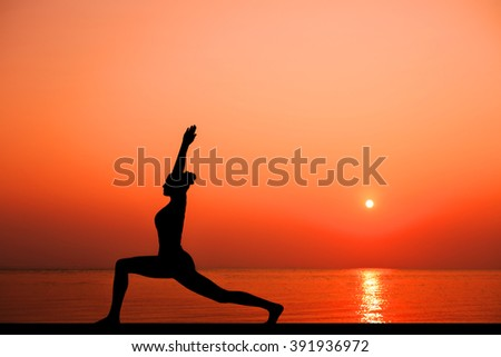 Silhouette of woman on the background of the stunning sea and sunset. Yoga, fitness and healthy lifestyle. Woman doing yoga exercises near the ocean.