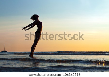 silhouette of woman on the sea - stock photo