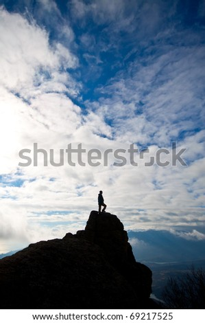 Silhouette of woman on the top of the rock - stock photo
