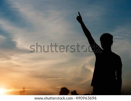 silhouette of woman pointing with finger in sky