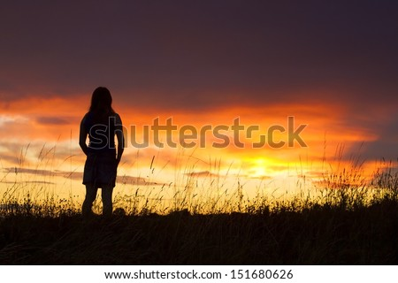 Silhouette of woman posing at sunset - stock photo