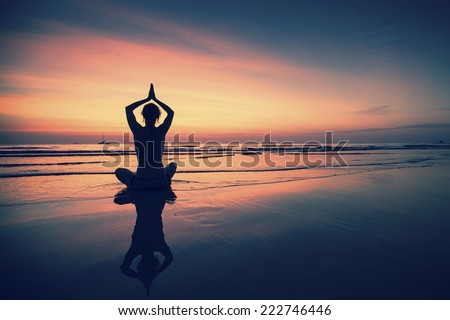 Silhouette of woman practicing yoga during surrealistic sunset at the seaside.