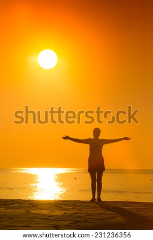 silhouette of woman practicing yoga with raised arms on the sunset   - stock photo