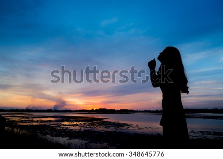 Silhouette of woman pray at sunset