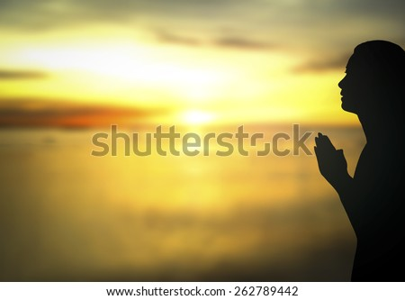 Silhouette of woman praying over beautiful autumn sunset with amazing golden light background. Pray for support, Thanksgiving, Christmas, Forgiveness, Repentance, Redeemer concept. - stock photo