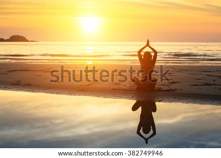 Silhouette of woman sitting on the beach during a beautiful sunset, with reflection in the water.