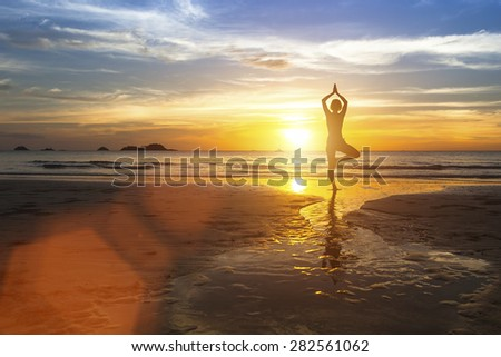 Silhouette of woman standing at yoga pose on the beach during amazing sunset. - stock photo