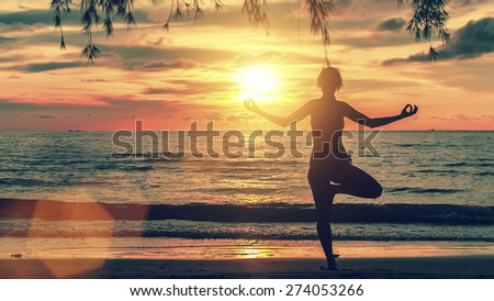Silhouette of woman standing at yoga pose on the beach during an amazing blood sunset.  - stock photo