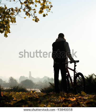 Silhouette of woman with bicycle with beautiful nature by the break of day - stock photo