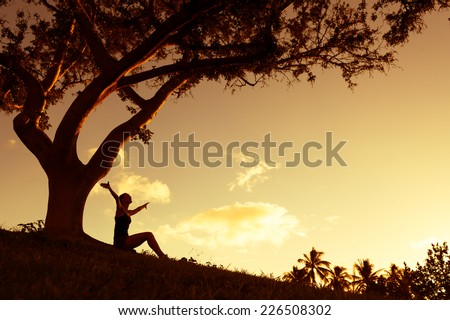 Silhouette of woman with hands raised into sunset - stock photo