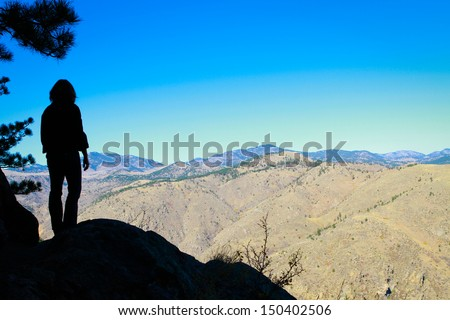 Silhouette of woman with mountain range in the background - stock photo