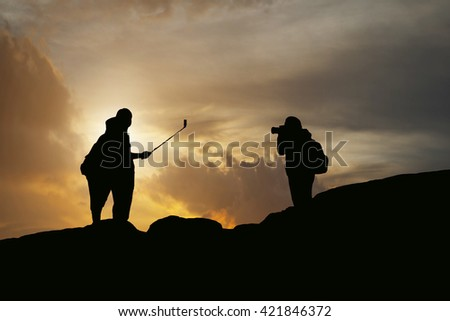 silhouette of women and man take photography and selfie with mountain at sunset .