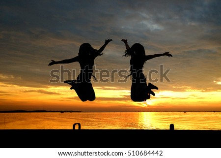 silhouette of women jumping at the sea with beautiful sunset background