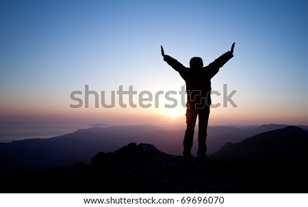 silhouette of women meeting sunrise on the top of mountain - stock photo