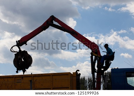 Silhouette of worker at hydraulic handling arm - stock photo
