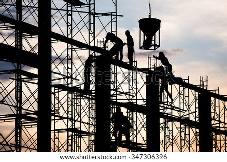 Silhouette of worker. Construction Building casting concrete work on scaffolding. - stock photo