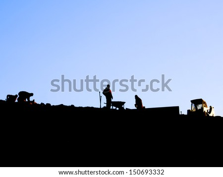 Silhouette of workers on a ridge with blue mauve sky background - stock photo