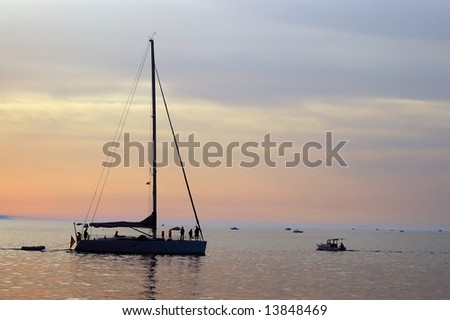 Silhouette of yacht coming into harbour - stock photo