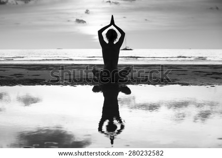 Silhouette of yoga woman on sea coast, contrasting black and white photo. - stock photo