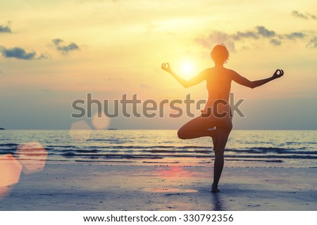 Silhouette of yoga woman on sea sunset. - stock photo