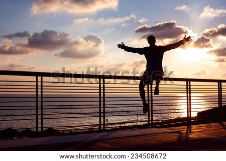 silhouette of young and active sportsman sitting on the railing with outstretched arms near the ocean and looking far away at the sunset  - stock photo