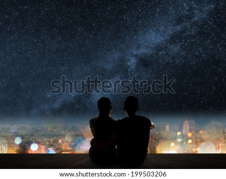 Silhouette of young Asian couple sit on wooden ground above the city under stars. - stock photo