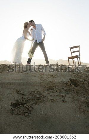 Silhouette of young beautiful couple enjoying an afternoon on beach sand dune  - stock photo