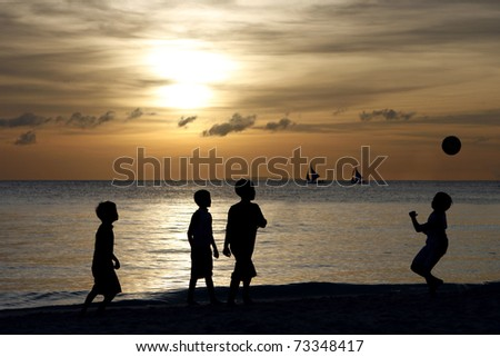 Silhouette of young boys playing during sunset at Boracay beach in the Philippines. - stock photo