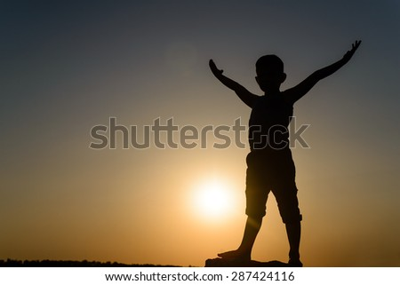 Silhouette of Young Carefree Boy Standing with Open Arms Raised in Air, Backlit By Late Day Sun with Copy Space