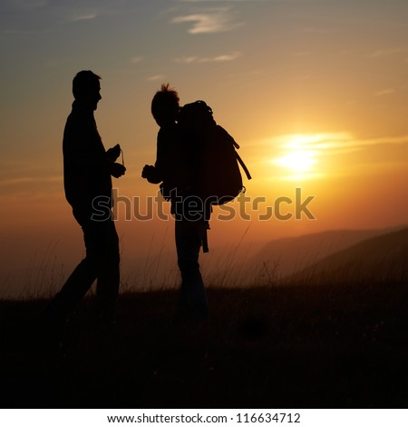 Silhouette of young couple against orange sunset