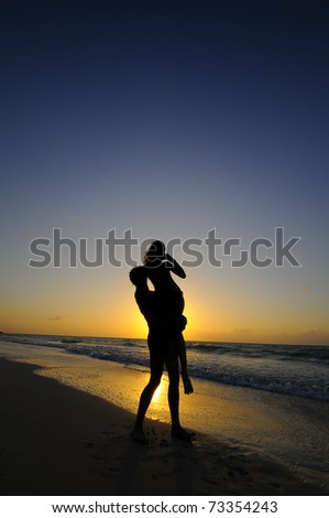 Silhouette of young couple on tropical beach at sunset